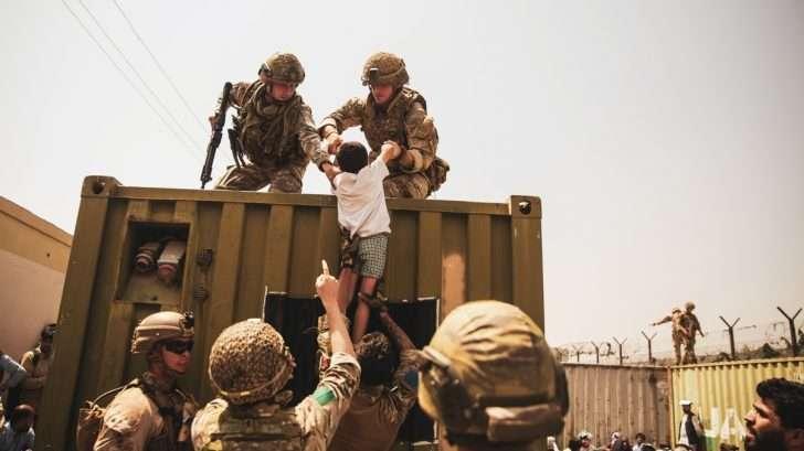 Britiske og tyrkiske koalitionsstyrker samt amerikanske marinesoldater hjælper et barn under en evakuering i Hamid Karzai International Airport, Kabul, Afghanistan, 20. august. Foto af Staff Sgt. Victor Mancilla